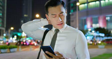 asian businessman feel neck pain on the street in the evening 版權商用圖片