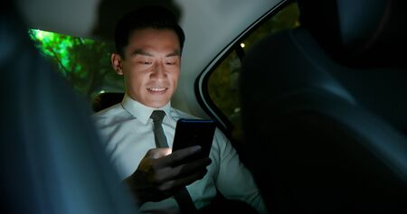 asian businessman use smartphone in the taxi