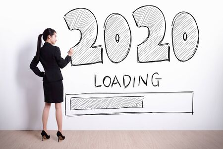 Back view of business woman writing 2020 new year on white wall background