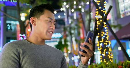 asian man use smart phone outdoor in the evening