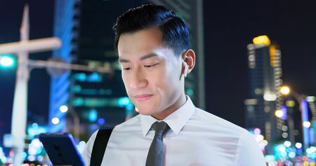 asian man wear wireless earbuds on and to listen music on the street 版權商用圖片