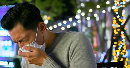 asian man feel sick and cough sitting on the outdoor chair