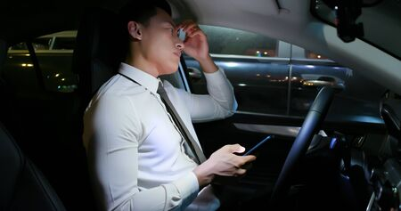 asian businessman feel tired and depressed after using smartphone in the car 版權商用圖片