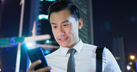 businessman use 5g smart phone outdoor in the evening