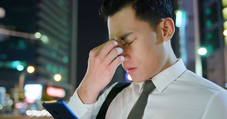 asian businessman feel eye tired while using smartphone on the street in the evening Фото со стока
