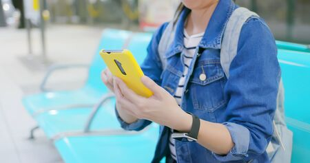 asian young woman use yellow smartphone on the mrt station