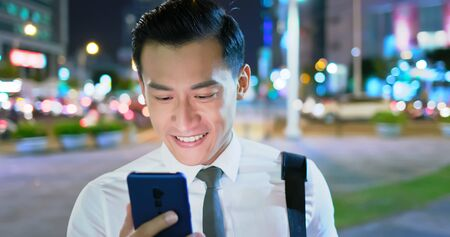 asian businessman use 5g smart phone outdoor in the evening