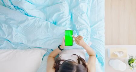 top view of asian woman use smartphone with green screen on the bed in the room