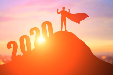 silhouette of super businessman feel excited with 2020 on the mountain