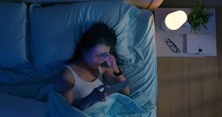High angle view shot of asian woman has eye pain and feel tired because watching smartphone in dark at night