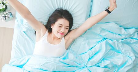 Top view of young beautiful asian woman sleeping well and stretching arm in the morning Banco de Imagens