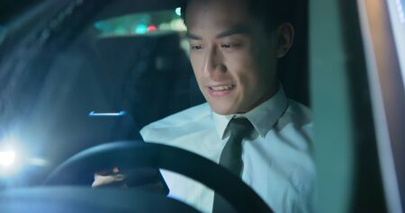 asian businessman use smartphone in the car