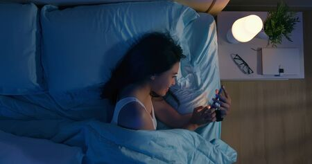 Top view of asian woman use smartphone on bed at night Фото со стока