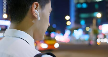 asian man listen music or speak to phone by wearing wireless earbuds while walking on the street Фото со стока