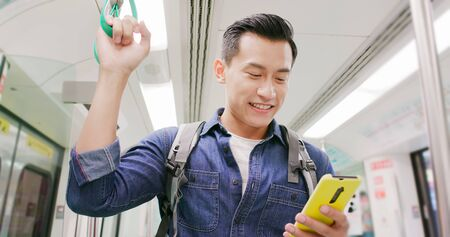 close up of asian young man use 5g smartphone on the mrt or train Stock Photo