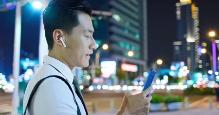 close up of asian man speak to phone by wearing wireless earbuds while walking on the street Фото со стока