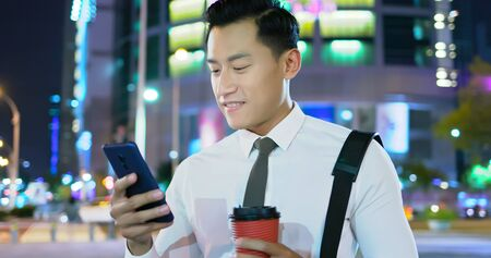 businessman walk and use 5g phone outdoor in the evening Фото со стока