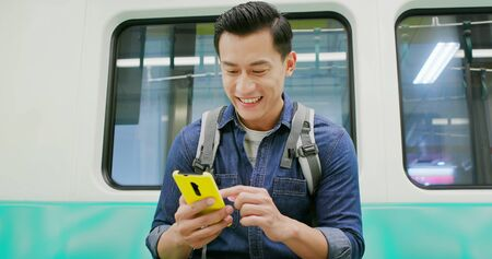 close up of asian young man use 5g smartphone on the subway Фото со стока