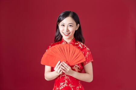 asian woman wearing cheongsam hold red envelopes and smile to you