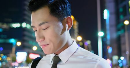 asian man wear wireless earbuds on and to listen music on the street Фото со стока