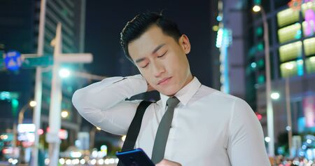 asian businessman feel neck pain on the street in the evening Фото со стока