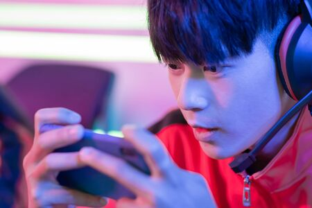 Close Up of young asian teenage cyber sport gamer play mobile game by smartphone on eSport tournament