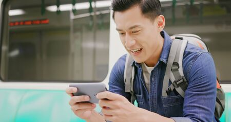 asian young man play game with 5g smartphone in the metro