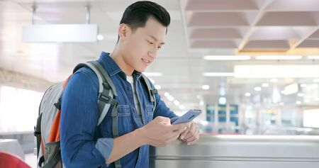 asian young man use 5g smartphone in the metro