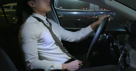 asian businessman get off work and fired from job sitting in his car