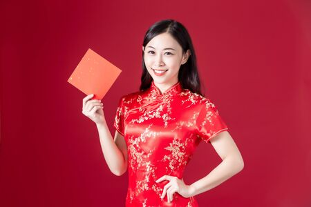 asian woman wearing cheongsam hold chinese spring festival couplets and smile to you