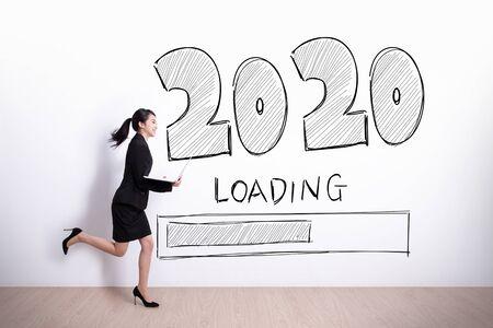 Erfolgreiche Geschäftsfrau, die Laptop mit 2020-Text und weißem Wandhintergrund läuft und hält