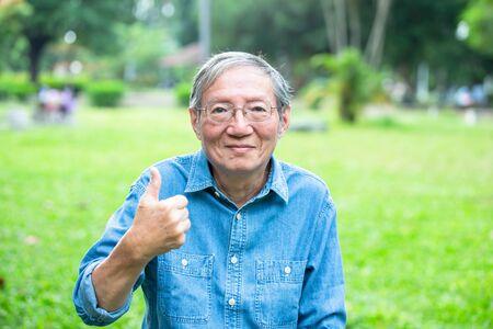 Aziatische oudere man zit in het park en met een duim omhoog gebaar