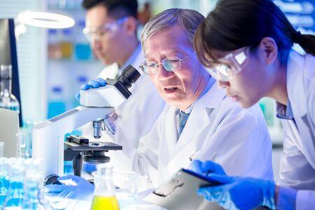 Reunión del equipo científico asiático y redacción de los resultados del análisis en el laboratorio. Foto de archivo