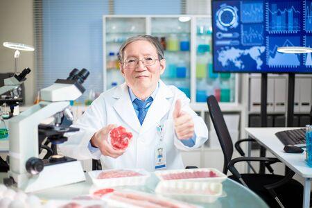 asian elder scientist take beef meat sample with good sigh gesture in lab