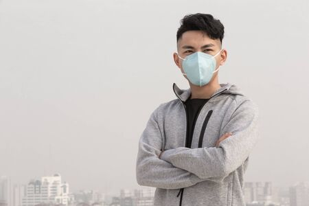Asian man wearing protective n95 mask due to urban air pollution or infectious disease Stock Photo