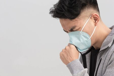 Asian man coughs and wears protective n95 mask because of air pollution or transmissible infectious diseases with gray background