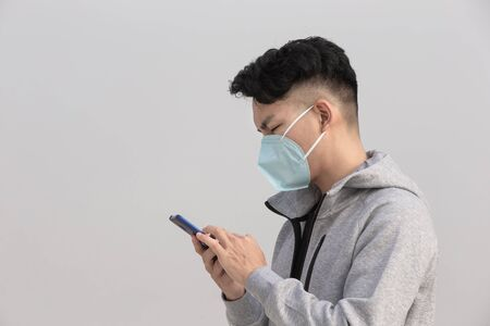 Asian man use smartphone and wears protective n95 mask because of air pollution or transmissible infectious diseases with gray background