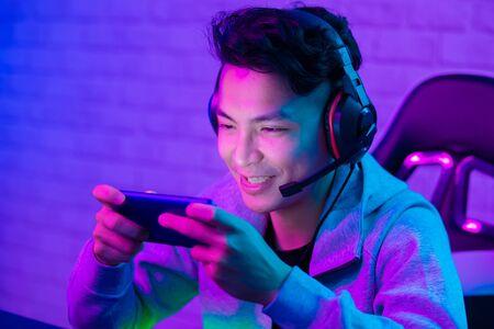 Jeune vlogger asiatique beau ayant une diffusion en direct et jouant à un jeu vidéo en ligne Banque d'images