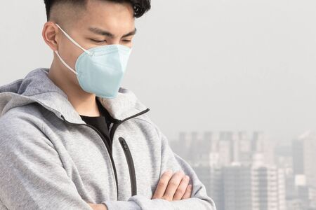 asian man feel depress and wears protective n95 mask because of air pollution or transmissible infectious diseases in the city