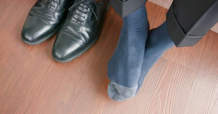 business man feel the feet itchy with athlete foot problem when take off shoes