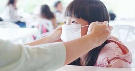 Asian parents wear masks to their children because of transmissible infectious diseases indoor in the crowd