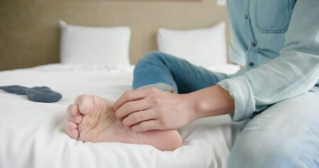 man scratch the itch by hand with athlete foot problem in the room