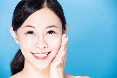 asian beauty woman apply lotion or sunscreen on her face and smile to you