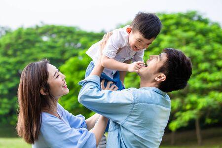 Vater hält Junge in seinem Arm und Eltern spielen mit Kind im Freien
