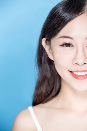 beauty woman smile happily with health teeth on the blue background