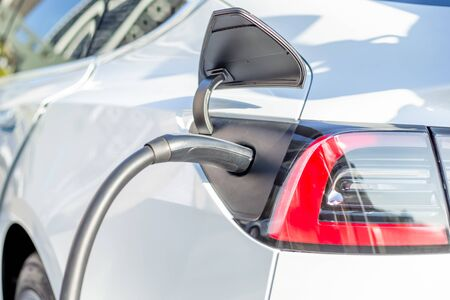 close up of power supply plugged into an electric car being charged