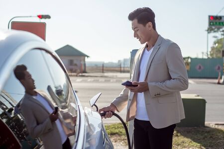 asian man use smart phone while waiting and power supply connect to electric vehicles for charging the battery in car