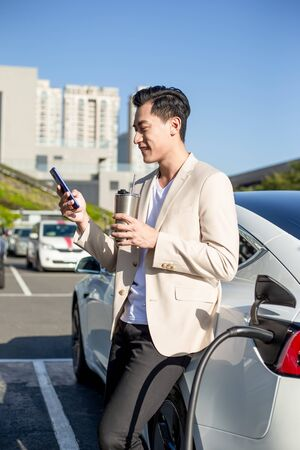 asian man use reusable eco-friendly ecological straw drink while using smart phone and waiting power supply connect to electric vehicles for charging the battery in car