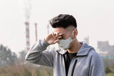 asian man wears protective n95 mask and has itchy eyes because air pollution in front of factory
