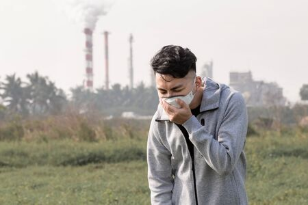 asian man coughs and wears protective n95 mask because air pollution standing in front of factory